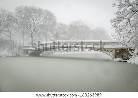 Wintertime in Central Park. Winter tree silhouettes surround the Bow Bridge and the Lake during an early morning snow fall in peaceful Central Park, Manhattan, New York. - stock photo