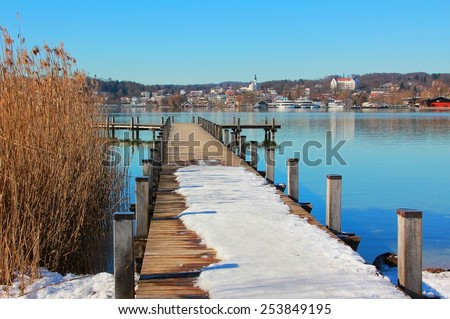 wintry boardwalk with snow at starnberg lake with view to the village, germany - stock photo