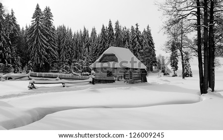 wintry country with cottage, stream, wood and flat country snow covered - stock photo