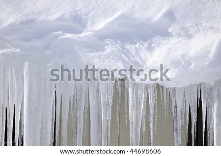 Wintry Icicles Hanging from Roof Horizontal With Copy Space - stock photo