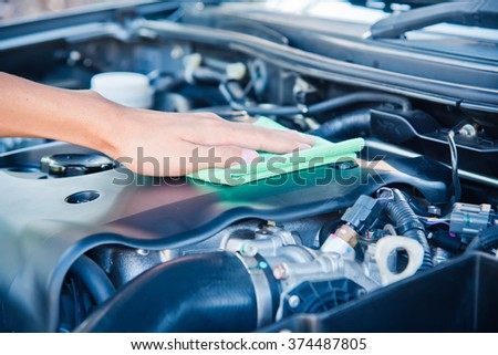 Wipe cleaning the car engine with green microfiber cloth  - stock photo