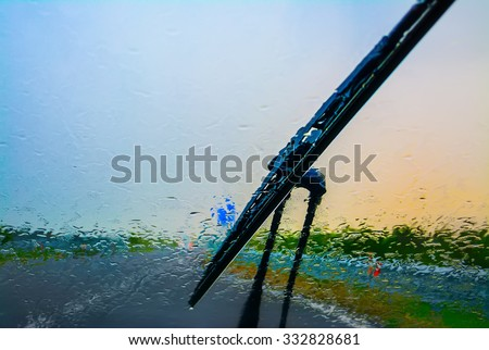 wiper on a wet windshield at sunset - stock photo