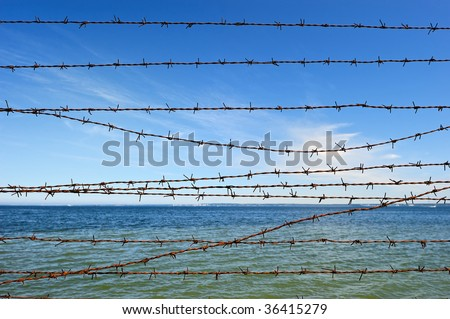 Wire entanglement on the background of sky and sea - stock photo