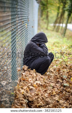 wire fence in front sad young man sitting - stock photo