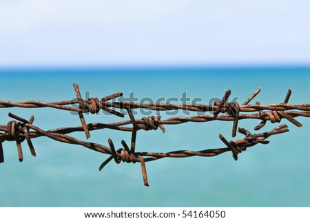wire fence on the beach - stock photo