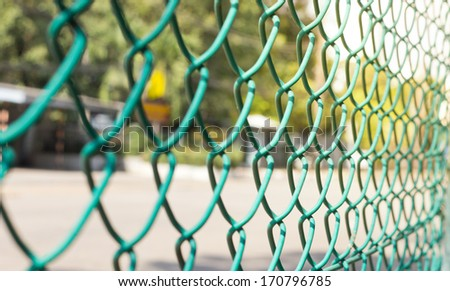 Wire fence with futsal field on background - stock photo