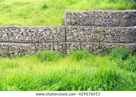 Wire mesh reinforcement with rock and green grass - stock photo