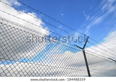 wired fence and blue sky in background - stock photo