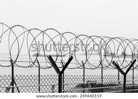 Wired fence with rolled barbed wires - stock photo