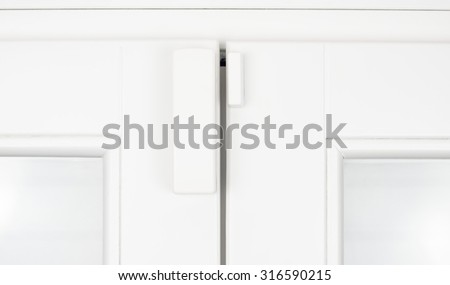 Wireless battery magnetic alarm sensor for window and door on white wooden sash detail - stock photo
