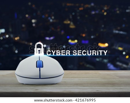 Wireless computer mouse with key icon and cyber security text on wooden table in front of blurred light city tower - stock photo