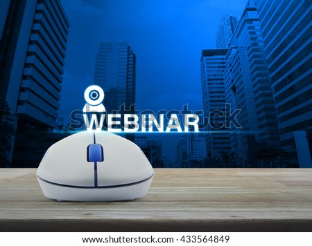 Wireless computer mouse with webinar icon on wooden table in front of city tower background, Seminar online concept - stock photo