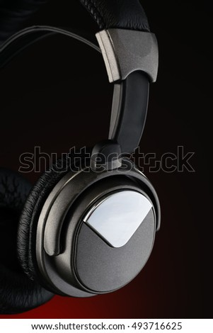 Wireless headphones isolated on black and red background