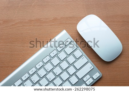 wireless keyboard and wireless mouse on wooden table - stock photo