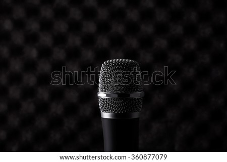 Wireless microphone closeup on foam rubber acoustic treatment background