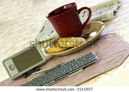 Wireless mobile office concept with brushed metal pda computer, portable keyboard, coffee, snack and newspaper. - stock photo