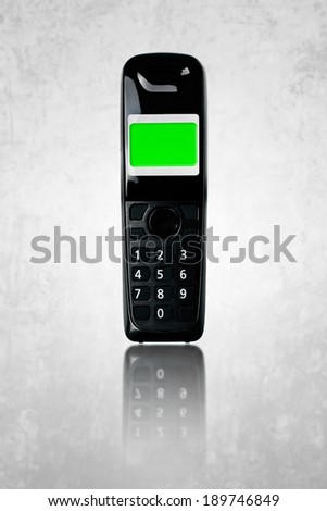 Wireless phone. Cordless phone with green screen display on grunge background. - stock photo