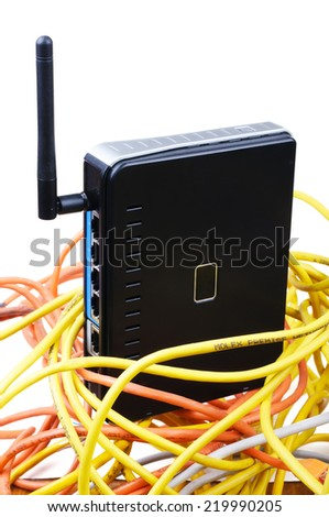 Wireless router among tangled network twisted wires. Isolated on white background. - stock photo