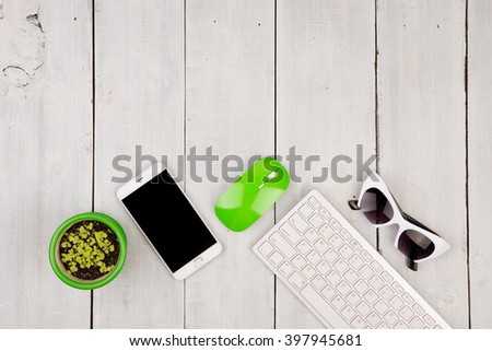 Wireless slim white keyboard and green mouse, smartphone, glasses, flower on white wooden background - stock photo