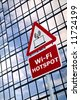Wireless technology concept image of a WiFI Hotspot sign outside a modern office building. (The wireless laptop icon was designed by myself.) - stock photo
