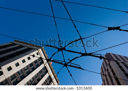 wires and skyscrapers against a deep blue sky - stock photo