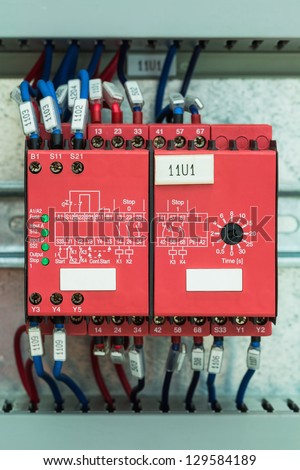 Wiring with marks on safety relays for emergency stop control in control cubicle - stock photo