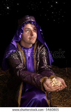 Wise man arrayed in majestic purple robe woven with gold metallic thread is offering in his palms finest pure frankincense. Focus to face. - stock photo
