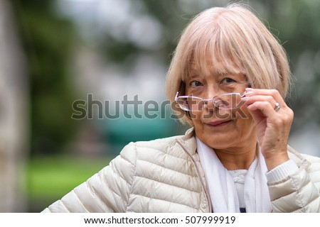 Wise old Japanese lady peers over her glasses at the camera