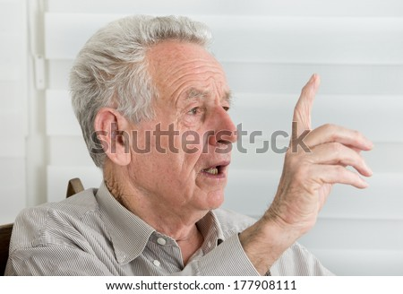 Wise old man talking with forefinger up in the air - stock photo