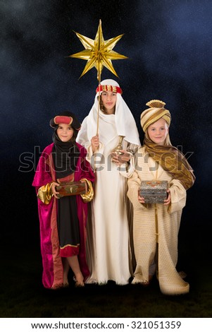 Wisemen played by three girls in a live Christmas nativity scene - stock photo