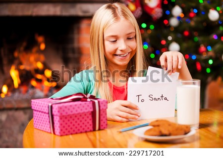 Wish list to Santa. Cute little girl putting a letter to Santa into the envelope while sitting at home with Christmas tree and fireplace in the background - stock photo