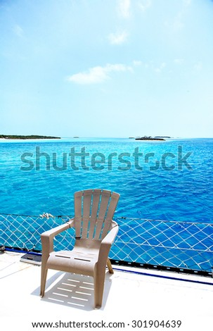 Wish you were here concept with empty chair against a tropical ocean