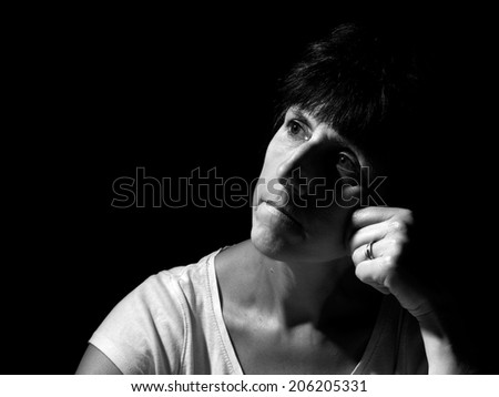 Wishes and regrets. Mature woman portrait, pensive, thoughtful. Strong  Rembrandt style lighting. - stock photo