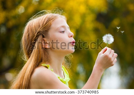 wishes,  happy child blowing dandelion in summer.  - stock photo
