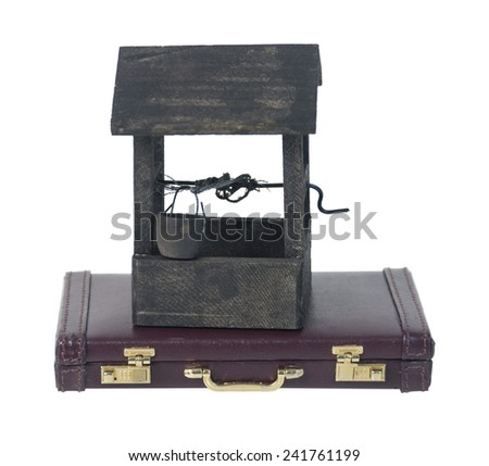 Wishing well with bucket to cast wishes into and a briefcase - stock photo