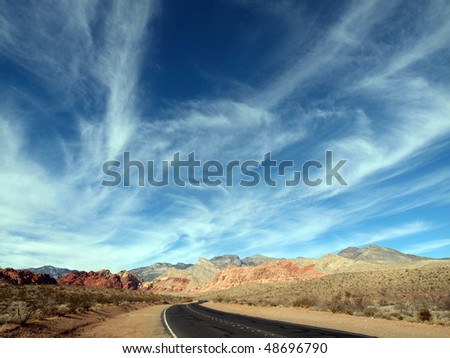 Wispy clouds over red rocks and highway in the vast deserts of Nevada, USA. - stock photo