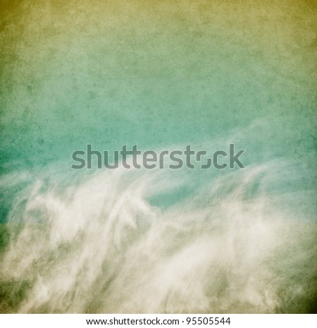 Wispy spring clouds on a textured, vintage paper background with grunge stains. - stock photo