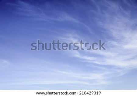 Wispy, thin cirrus clouds against blue sky - stock photo