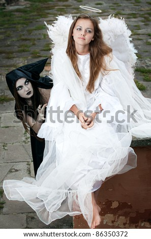 witch and angel against the walls of the old castle - stock photo