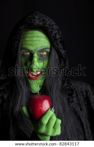 Witch and her poisonous apple, black background. - stock photo