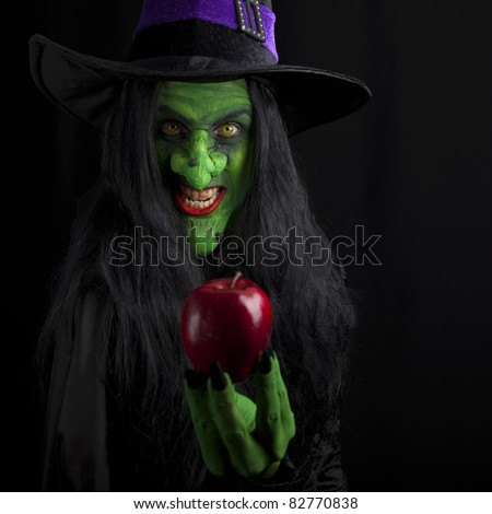 Witch and her poisonous red apple, black background. - stock photo