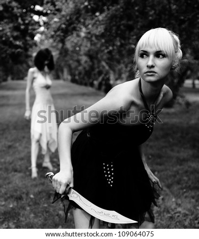 witch and young warrior woman with sword at forest - stock photo