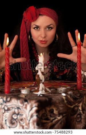 Witch at the table with candles. Isolated on black - stock photo