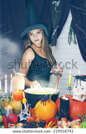 witch cooks a potion in a cauldron, throwing secret ingredient - stock photo