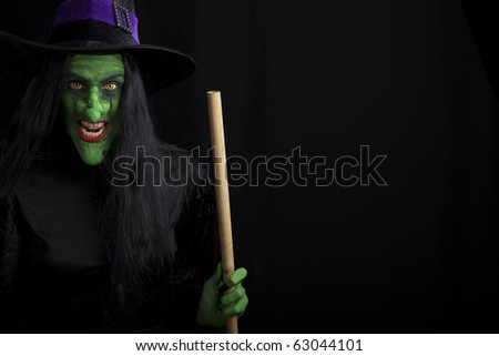 Witch holding a broomstick. Isolated on black. - stock photo