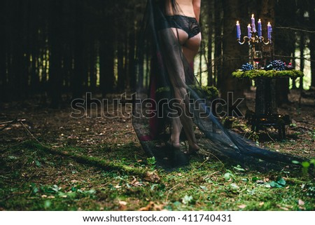 Witch in black cloak goes through a forest. Beautiful dark vampire woman with mantle.