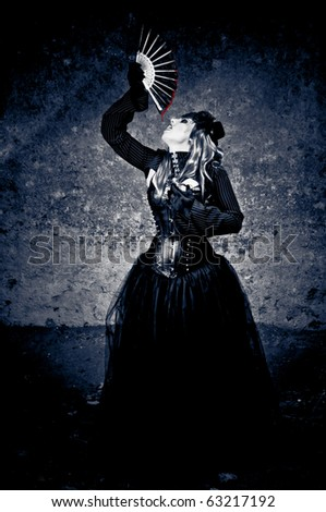 Witch in black dress drinking blood dripping from a fan - stock photo