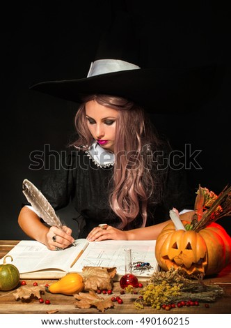 Witch in the hat at the table. He writes feather in the book. On a black background.
