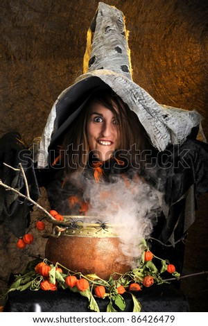 witch making faces and cooking in a copper cauldron