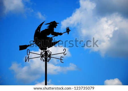 Witch on broomstick weather vane on blue sky background - stock photo